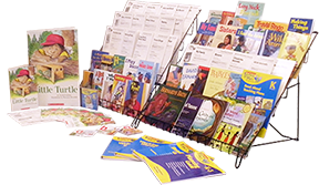 Image of kindergarten resources, some books in rack, others spread out on flat surface in front